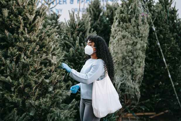 black woman in medical mask picking spruce tree