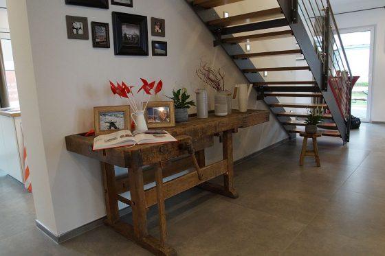 Unter der modernen Treppe wird der Raum mit einer antiken Hobelbank aus grobem Holz gut genutzt. Ein absoluter Blickfang, den man in einem neuen Haus zunächst nicht erwarten würde. (Foto: Markus Burgdorf)