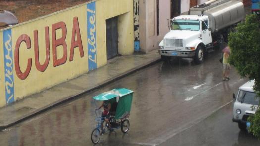 Ein Bici-Taxi fährt bei strömenden Regen durch Havanna