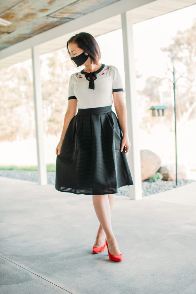 Wearing a cloth face mask with a black midi skirt by Pocket Passionista