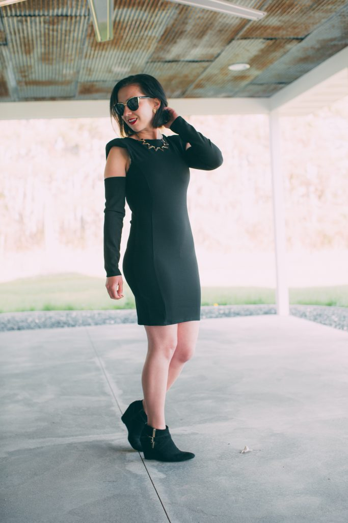 black dress with padded shoulders and cut out sleeves