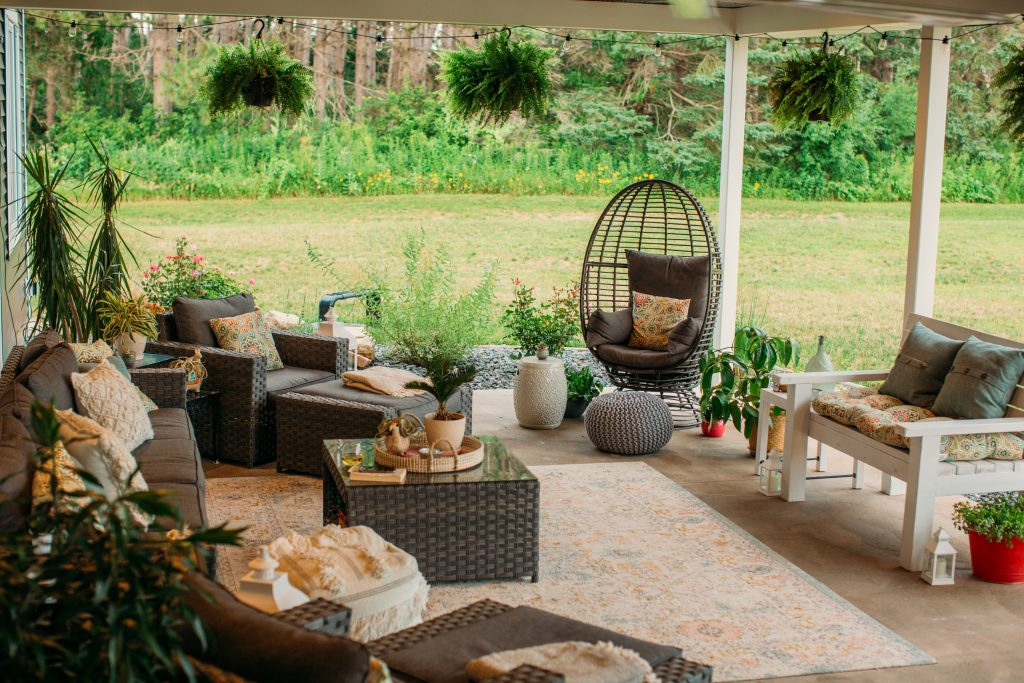 Backyard living comfortable boho chic outdoor living space with wicker furniture, ferns, egg chair