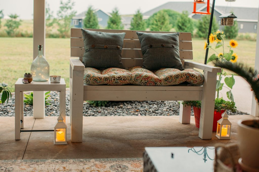 Decorative white garden bench with cushion and lanterns for backyard living space