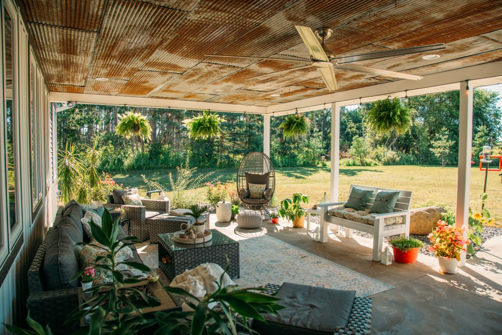 Boho chic outdoor living space with hanging boston ferns and air plants