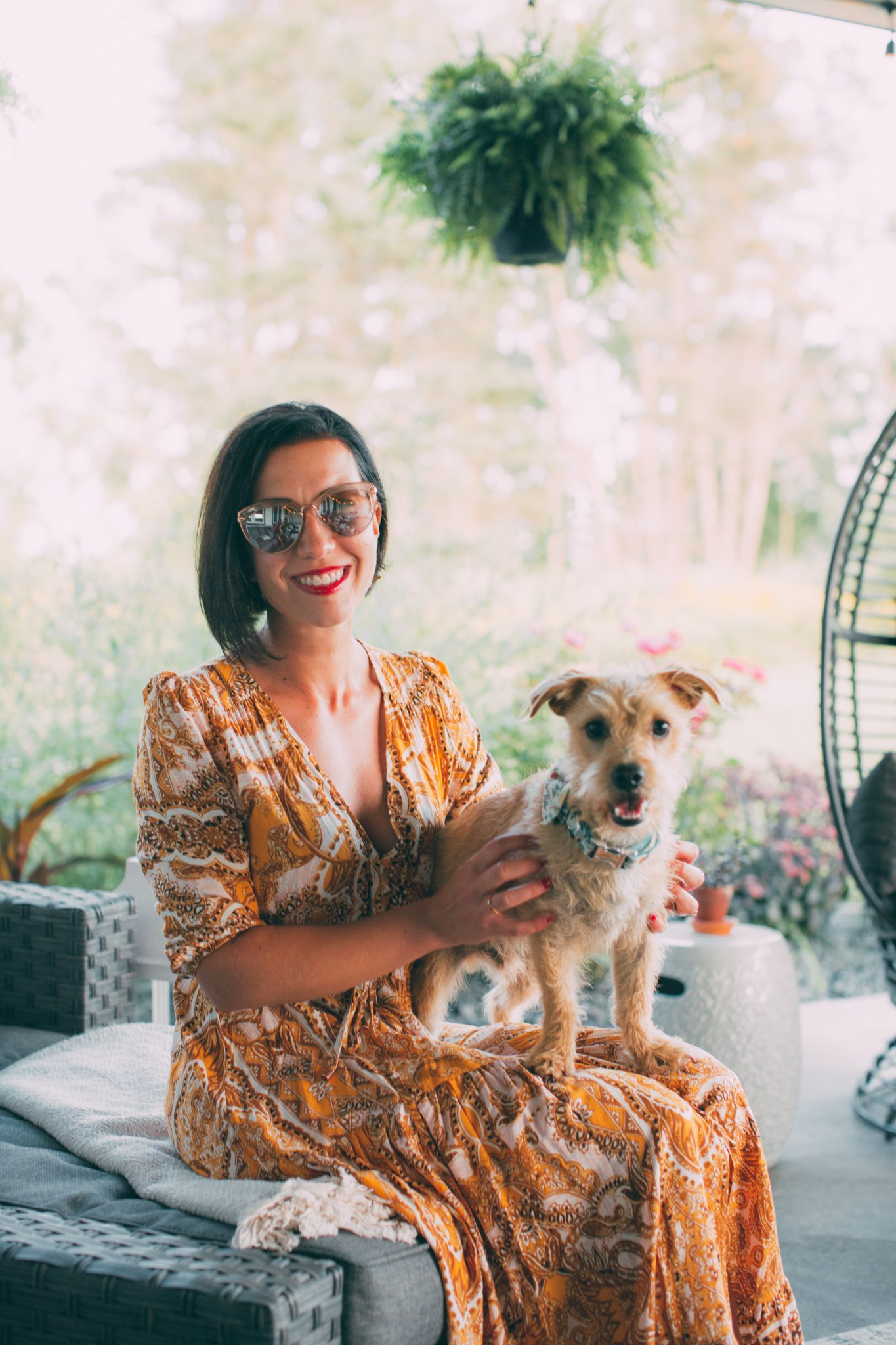 Lindsey of Have Clothes, Will Travel holding her puppy, Buddy, while wearing a yellow Salty Crush maxi dress