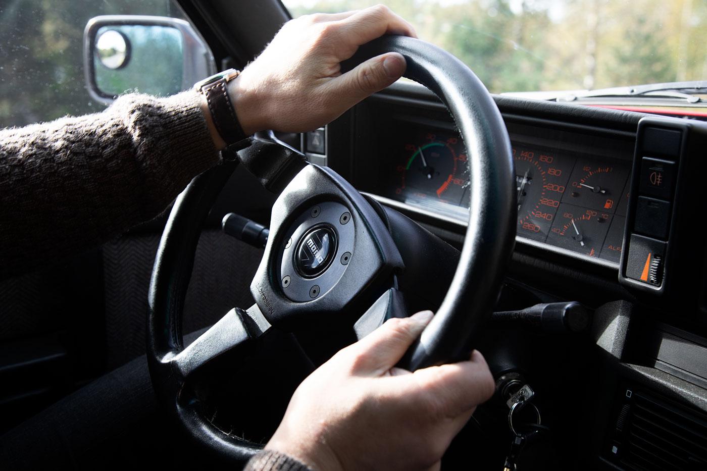 Alfa Romeo seiskavitonen ajossa sisältä. Lähikuvassa ratti ja miehen kädet.