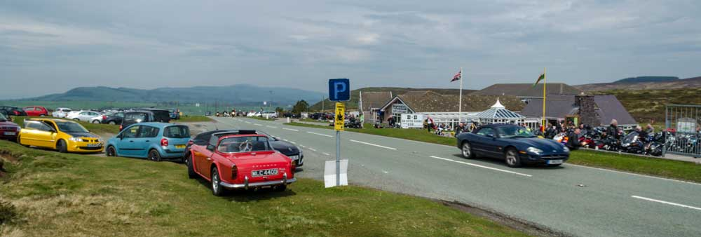 A wide variety of modern, old, sports and tourning cars jostle with motorbikes outside the Ponderosa Cafe