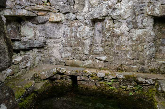 The bath house at St. Cybi's Well with the waters in the foreground and niches clearly visible.