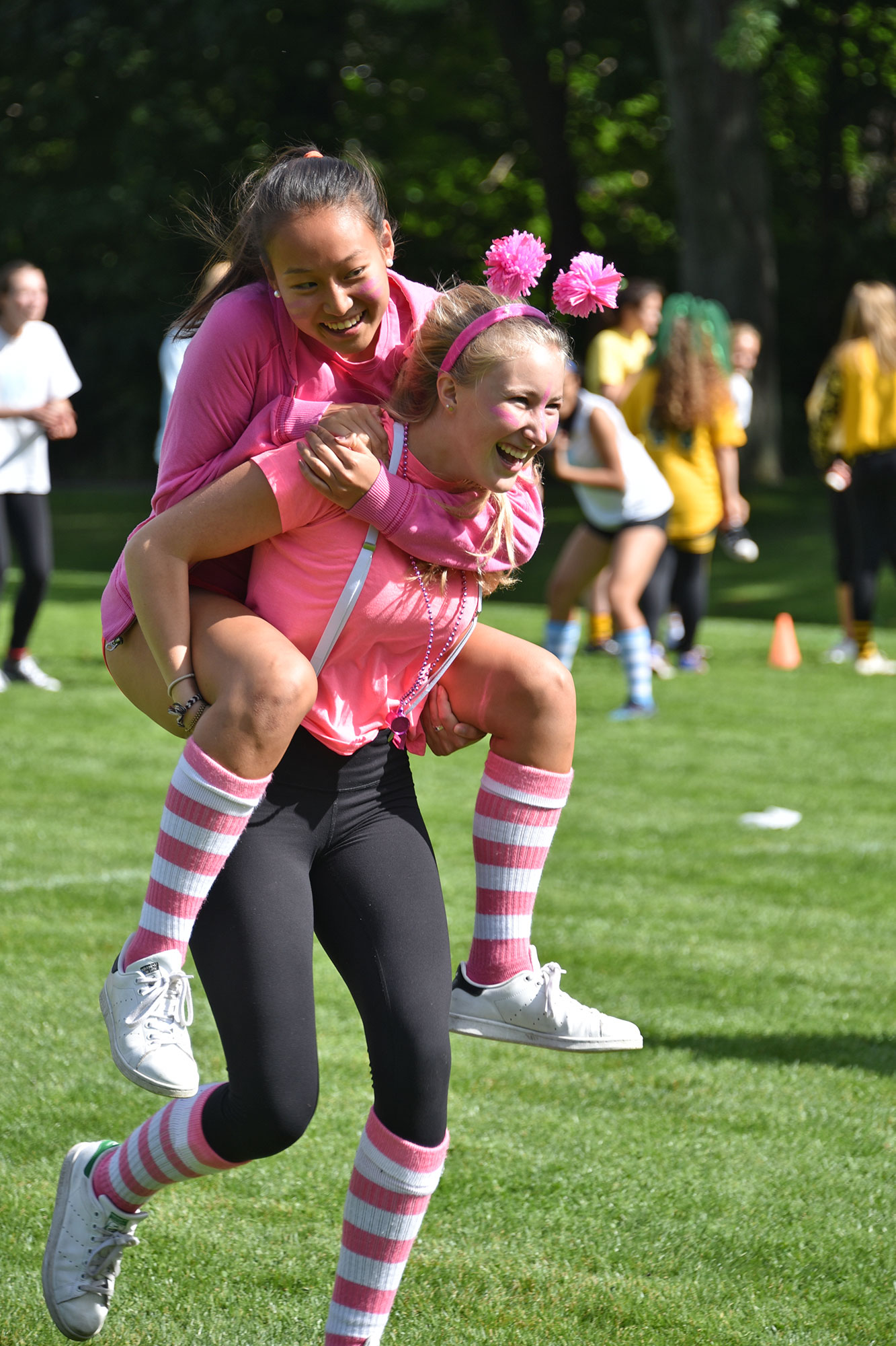 One student piggybacking another for a race on a field. Both are wearing pink and white for Agnes Hansen House.