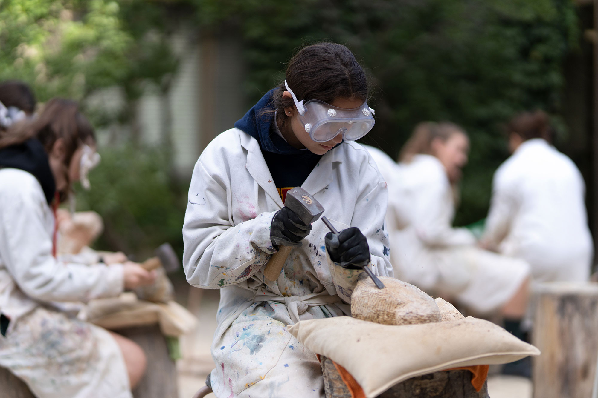 A student engaged in stone carving, wearing a white coat and safety glasses.