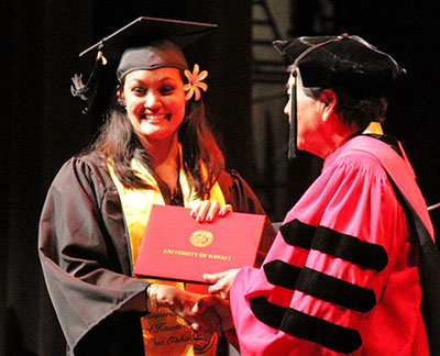 A student in cap and gown receiving diploma from chancellor