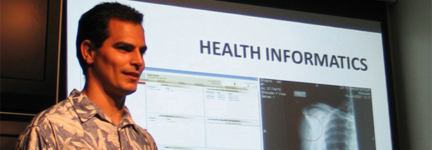 Man standing in front of a health informatics screen