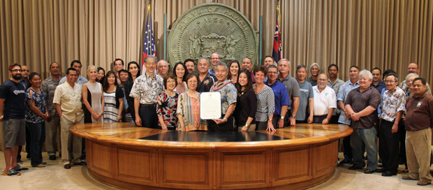 large group of people standing with Hawaii Governor Ige