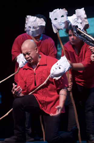 actors in red with white masks rehearsing
