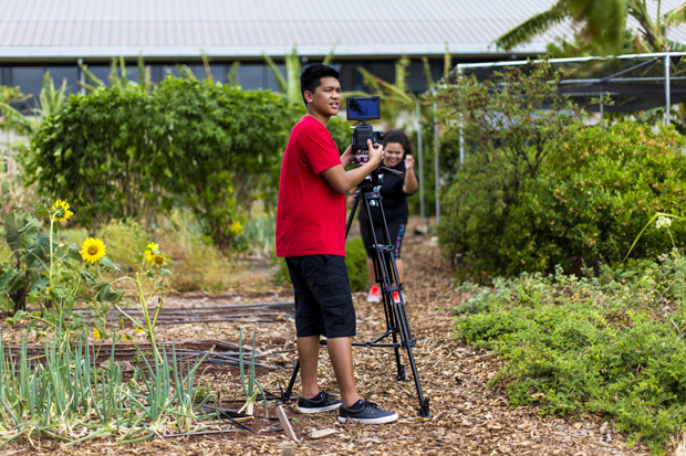 students filming in a garden