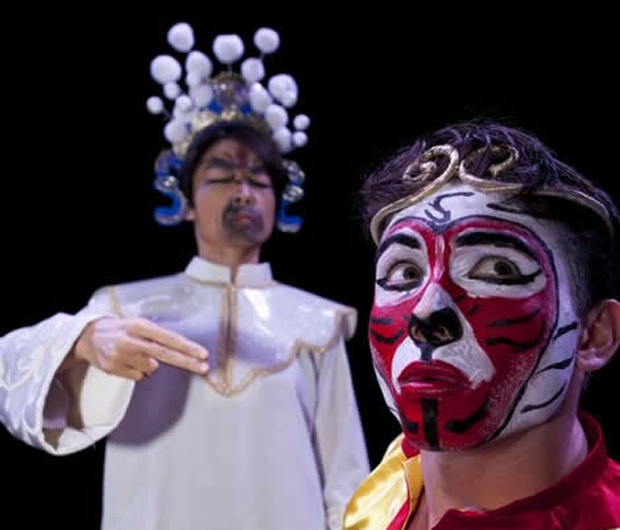 one actor in a white robe with elaborate crown and another, looking away in a bright red monkey mask