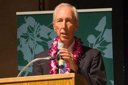 James Burns speaking at a podium