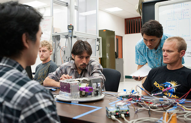 Students looking at Project Imua's payload