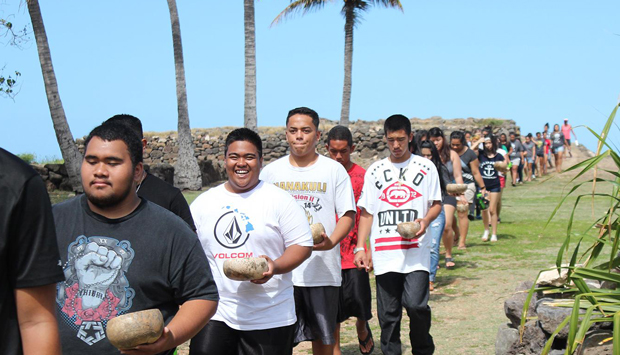Students in a line walking down from Heiau, each with a bowl in their left hand