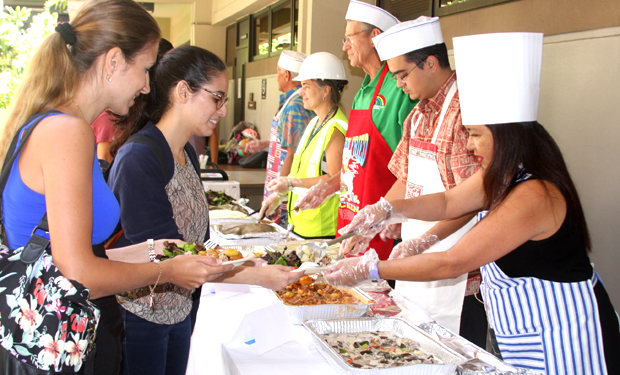 people serving stew to students