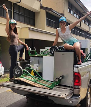 Two students posing on a truck with mini-fridges in the truck bed