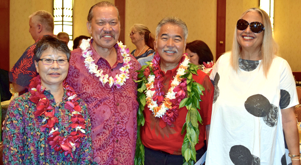 four people standing together wearing lei