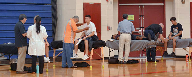Medical professionals examining students in a gym