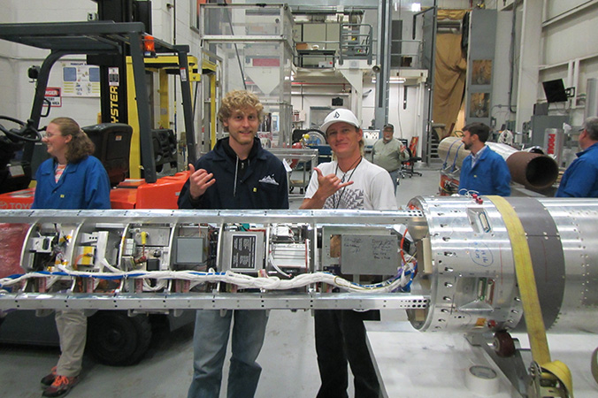 Two students flashing shaka with the integrated payload