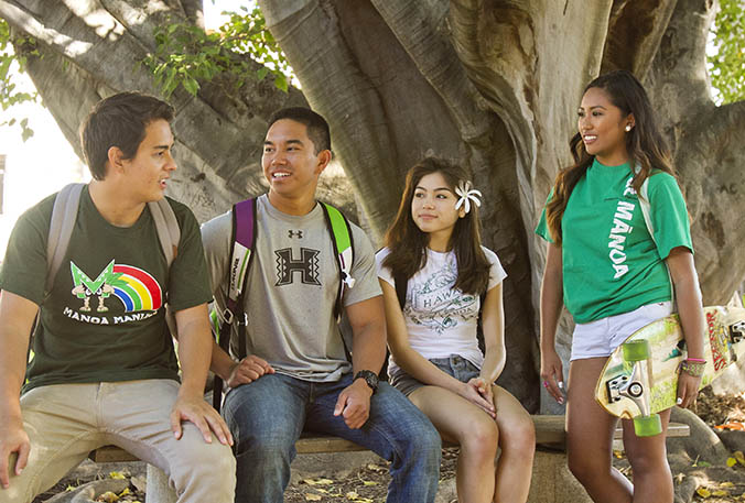 Four Manoa students sitting in front of a tree