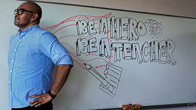 teacher in front of a whiteboard that says Be a Hero Be a Teacher