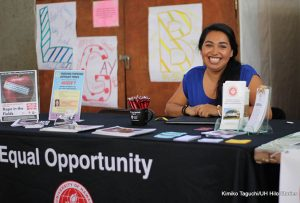 a smiling woman sitting at a Title IX table