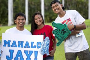 Smiling students holding a ʻMahalo Jayʻ sign