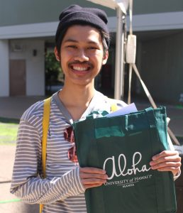 person holding UH Manoa informational bag