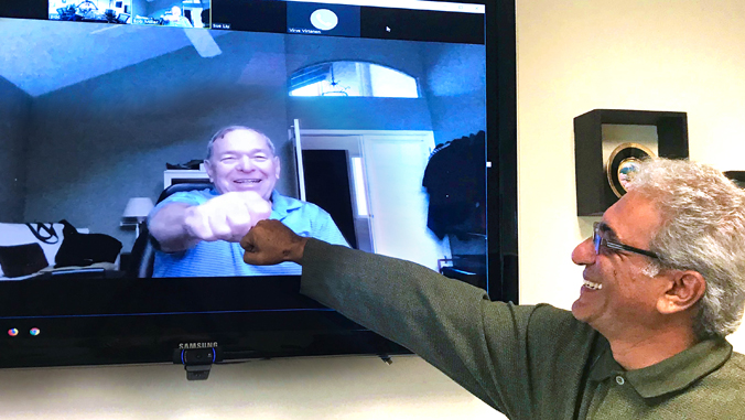 two people fist bumping over video conference