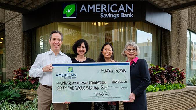 Four people holding an American Savings Bank check
