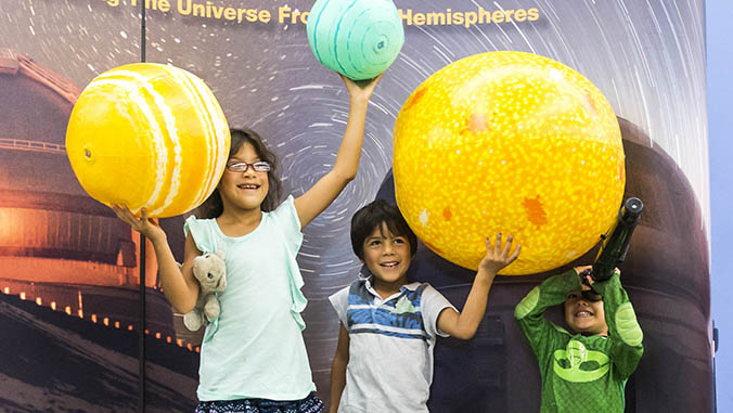 Kids holding up inflatable planets
