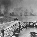 Soldiers depart from ships toward the shoreline through the blast zone