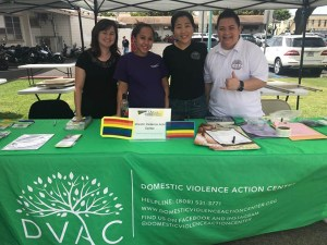 Volunteers smiling at the Domestic Violence Action Center info table