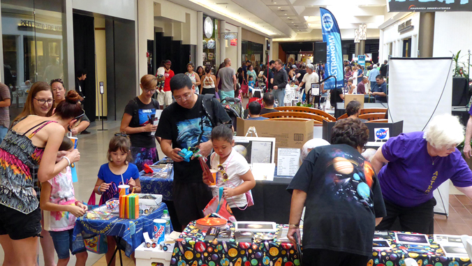 people participating at science displays in the mall