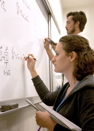 students writing math equation on a white board