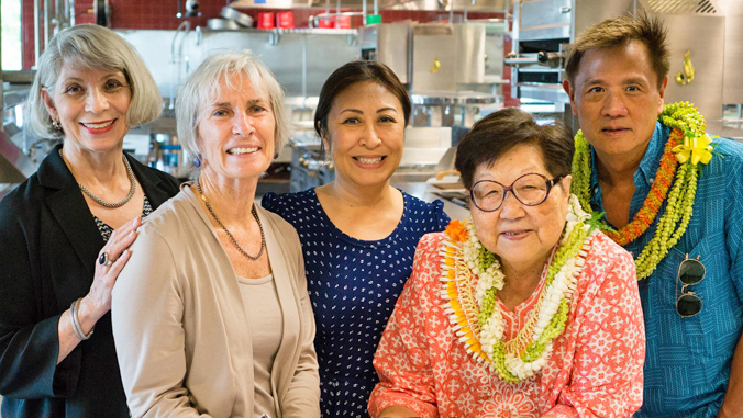five people standing in the Culinary Institute of the Pacific kitchen