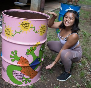 girl posing with decorated garbage can
