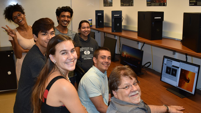teacher and students gather around new computers