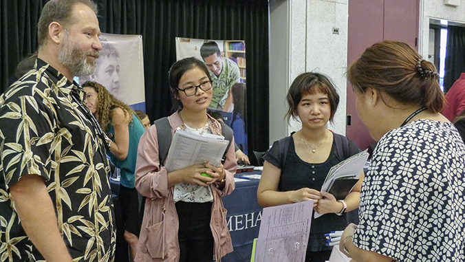 Students getting information at a table at the Career Fair