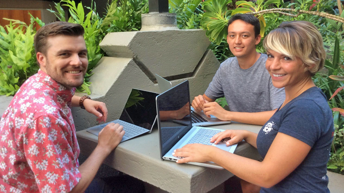 three law students sitting at a table with their laptops
