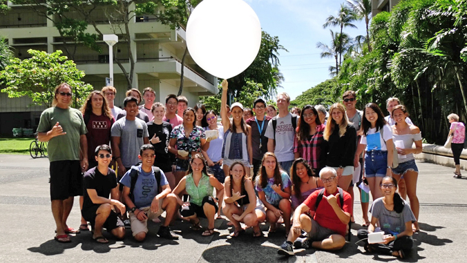 students and instructor posing with white weather balloon