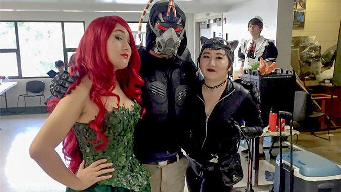 Students pose dressed as Poison Ivy, Bane and Catwoman