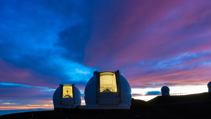 two telescopes on Maunakea against night time sky
