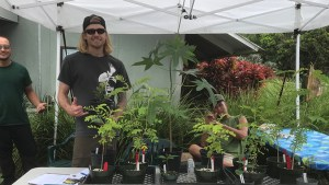 three males with various plants and trees
