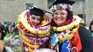 students in graduation regalia wearing lei